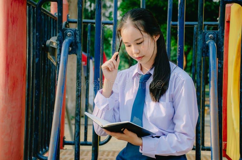 Mooie tiener die school eenvormig het schrijven boek dragen terwijl het denken met het zitten op een schommeling bij het park stock afbeelding