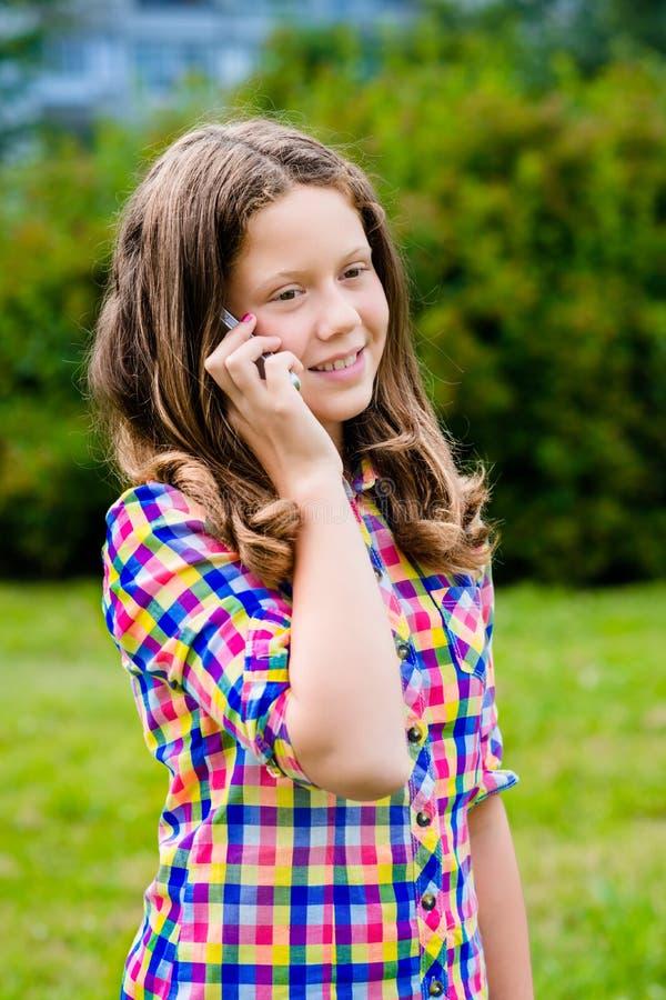 Mooie tiener die in vrijetijdskleding door celtelefoon spreken stock afbeeldingen
