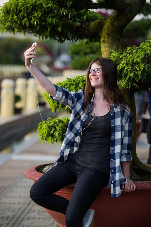 Mooie tiener die zwarte jeans en geruit overhemd dragen die een selfie op smartphone in openlucht in park nemen stock foto's