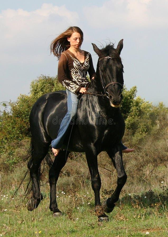 Mooie tiener en zwart paard stock afbeelding