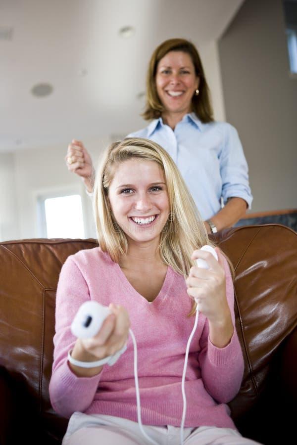 Mooie tiener het spelen videospelletjes thuis stock foto
