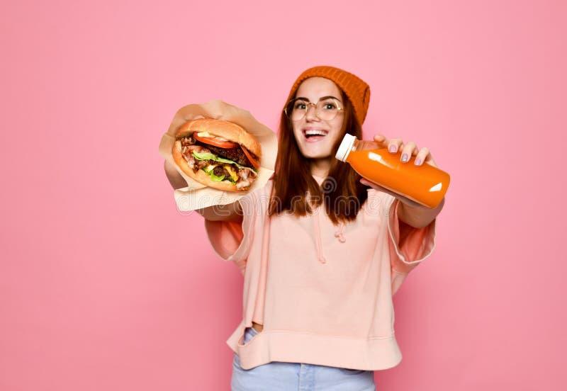 Mooie tiener met rode haar en hoedenholdingshamburger en drank in beide handen stock foto