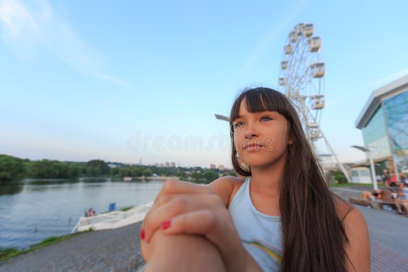 Mooie tiener in roze kleding met lang haar in een groen de zomerpark royalty-vrije stock afbeelding