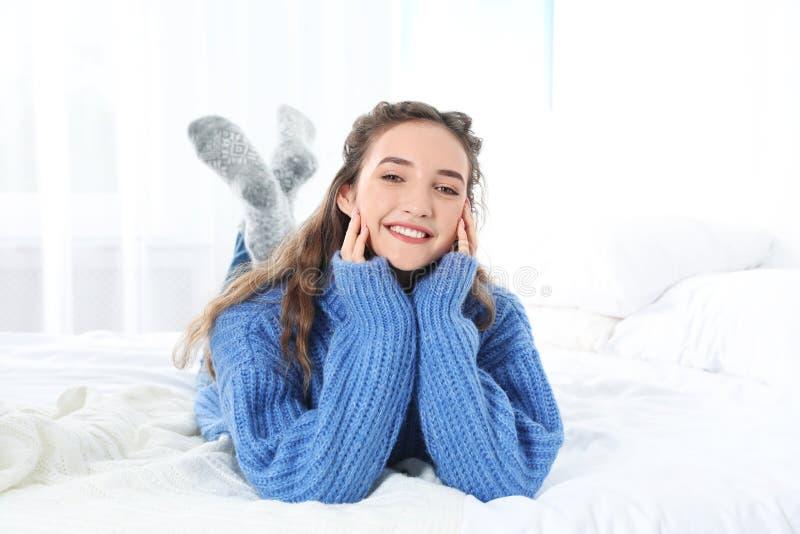 Mooie tiener in warme comfortabele sweater op bed royalty-vrije stock foto