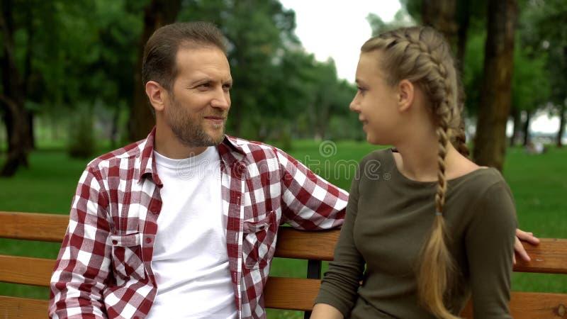 Mooie tienerdochter het vertellen geheimen aan vader, die op bank in park ontspannen stock foto