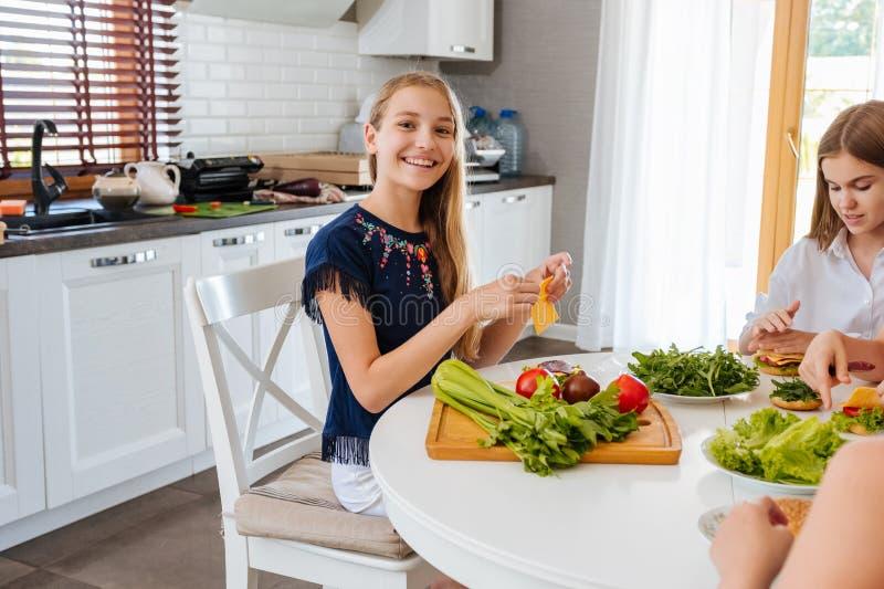 Mooie tieners die een gamburger in de keuken maken stock foto