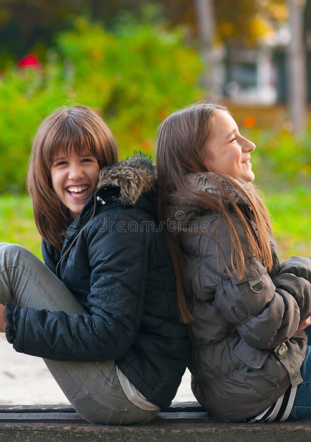 Mooie tieners die en in park lachen gekscheren stock foto's