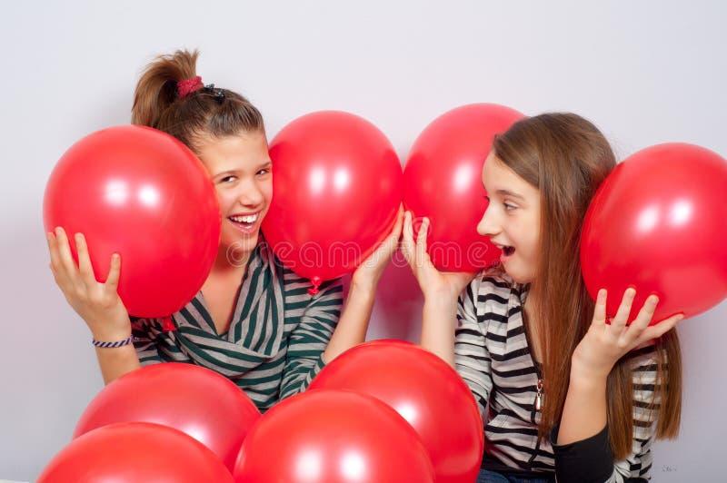 Mooie tieners die met rode ballons spelen stock foto's