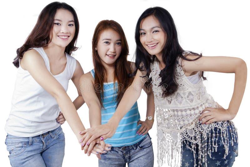 Mooie tienerstudenten die bij handen aansluiten zich royalty-vrije stock afbeeldingen