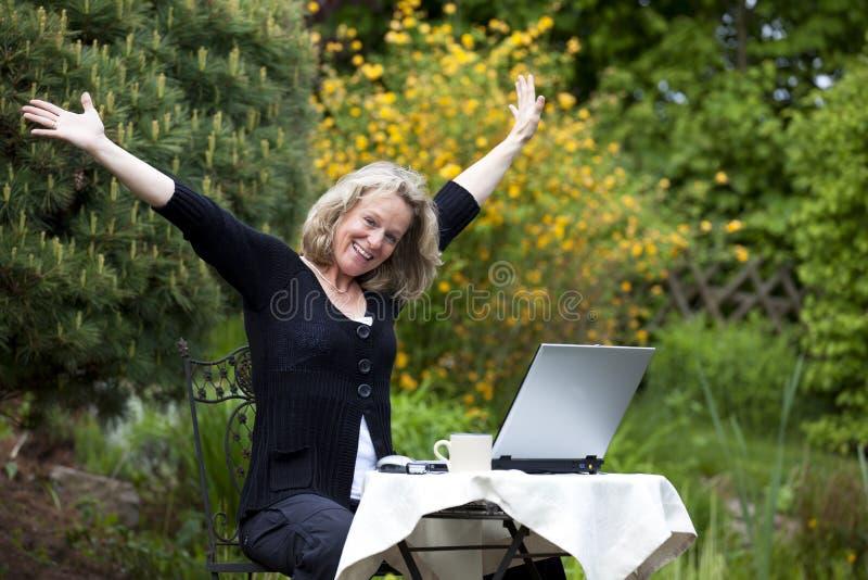 Mooie toejuichende blonde rijpe vrouw stock afbeelding