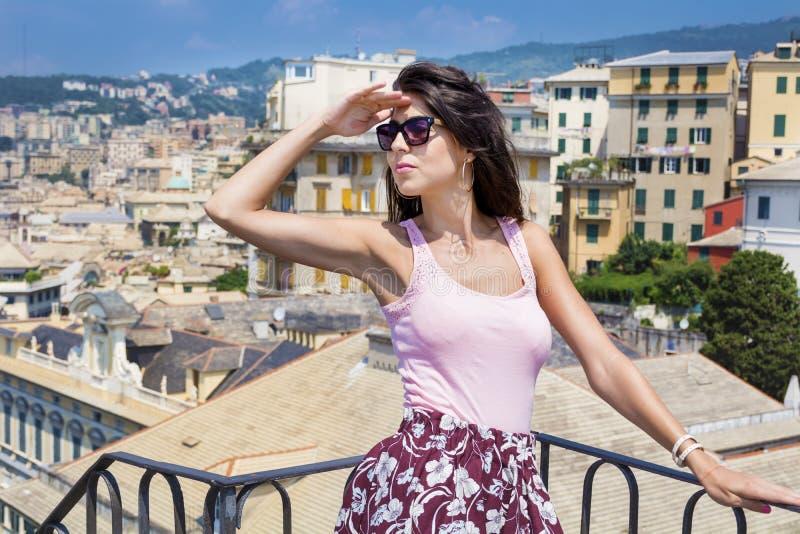 Mooie toeristenvrouw die aan de haven van Genua van balkon over de stad kijken royalty-vrije stock afbeelding