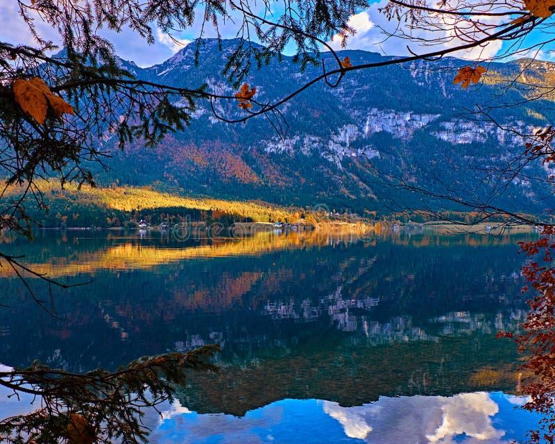 Mooie toneelzonsondergang bij het Oostenrijkse meer van alpen Oude uitstekende landelijke huizen en houten botenhuizen in alpen b stock fotografie