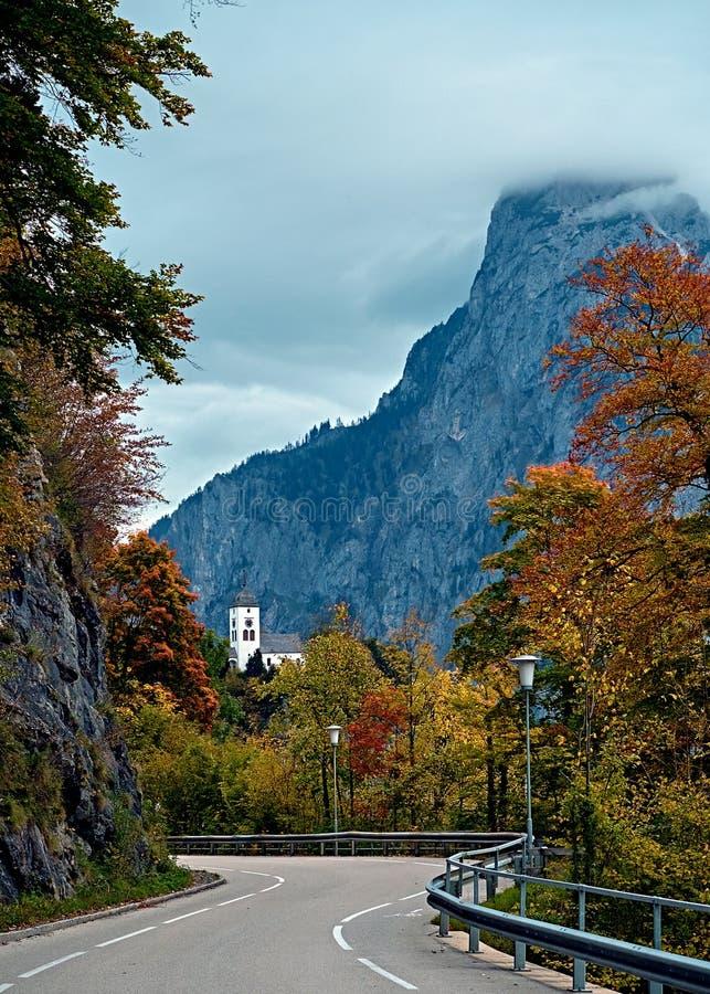 Mooie toneelzonsondergang over het Oostenrijkse meer van alpen Wegweg voor kerk op de rots met wolken over Traunstein-berg stock afbeelding