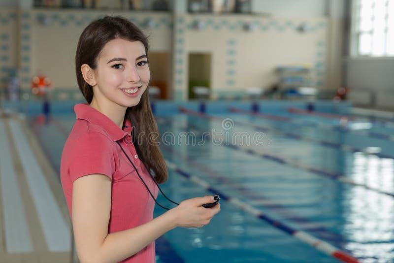 Mooie trainervrouw die een chronometer op poolside houden royalty-vrije stock foto
