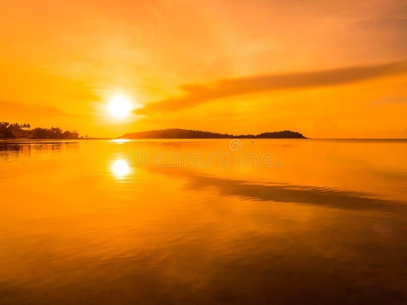 Mooie tropische strandoverzees en oceaan met kokosnotenpalm in zonsopgangtijd royalty-vrije stock afbeeldingen