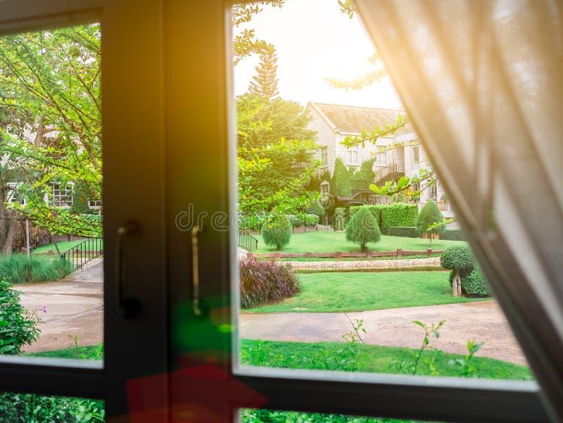 Mooie tuinaard achter de gloed van de vensterverlichting helder in de ochtend Wit kader en donker handvat Kijk door het glas stock fotografie