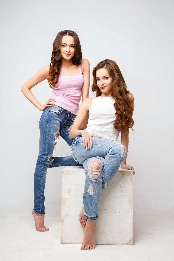 Mooie tweelingen jonge vrouwen in vrijetijdskleding over witte achtergrond Het Portret van de Manier van de schoonheid royalty-vrije stock fotografie
