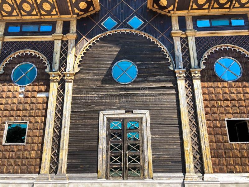 Mooie uitstekende oude oude gesneden authentieke deur met vensters met glas met een gesmede kaderbogen en patronen Achtergrond royalty-vrije stock fotografie