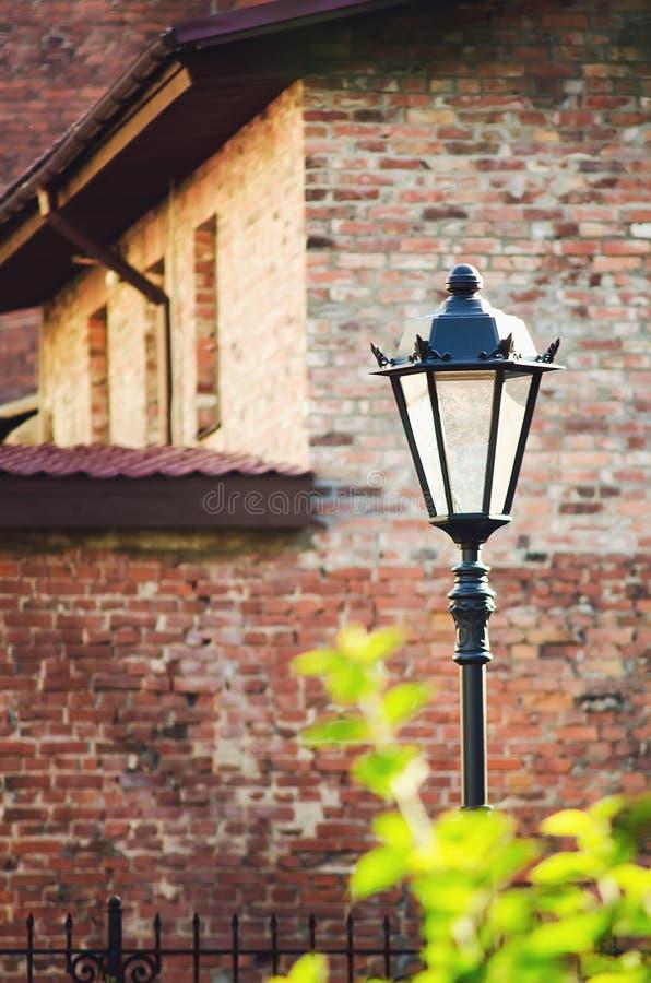 Mooie uitstekende straatlantaarn op de achtergrond van een oude bakstenen muur stock fotografie
