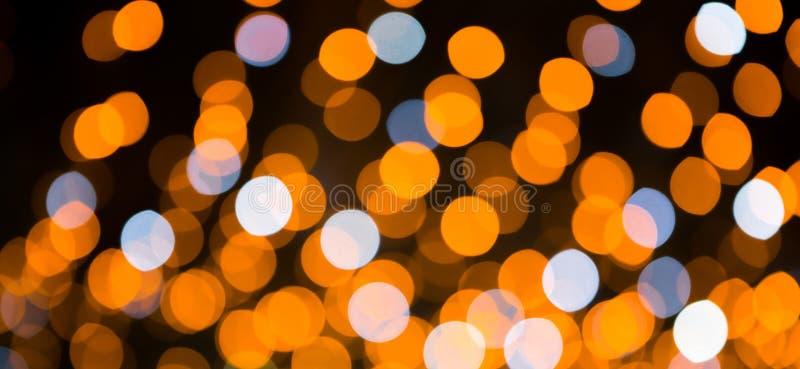 Mooie Vakantieachtergrond met heldere gele, oranje en blauwe bokehlichten Feestelijke textuur De Lichten van Kerstmis Vaag kleurr stock foto