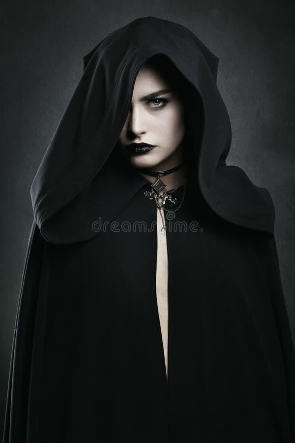 Mooie vampiervrouw met zwarte mantel royalty-vrije stock afbeelding