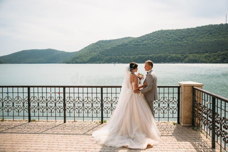 Mooie van de van de huwelijkspaar, bruid en bruidegom holdingshanden op een meerachtergrond Leuk meisje in lange witte kleding, m royalty-vrije stock fotografie