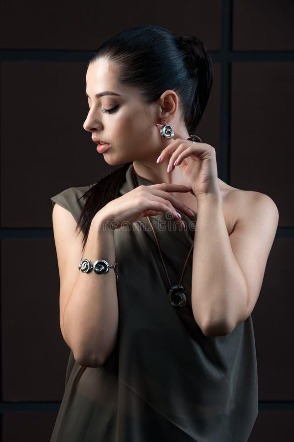 Mooie verfijnde donkere haired vrouw die elegante opzichtig dragen stock fotografie