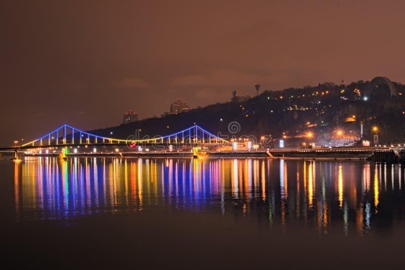 Mooie verlichting van VoetdieBrug in het water wordt weerspiegeld Avondmening over de promenade langs Dnieper stock afbeeldingen