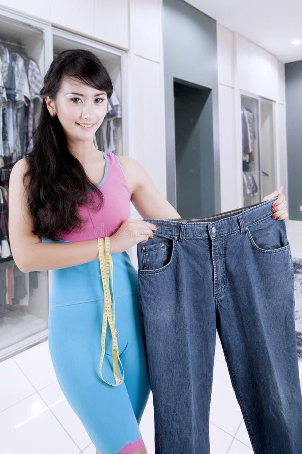 Mooie vermageringsdieetvrouw die haar oude jeans tonen stock foto