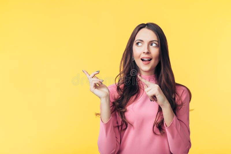 Mooie verraste vrouw die vinger richten op exemplaar het ruimte kijken weg geïsoleerd op gele achtergrond stock fotografie