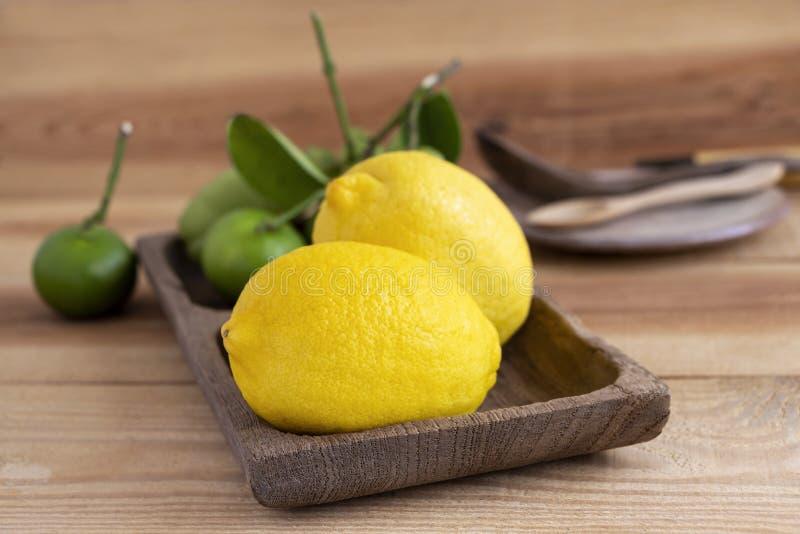 Mooie verse citroen die in een houten plaat op een houten lijst in de keuken wordt geplaatst stock foto's