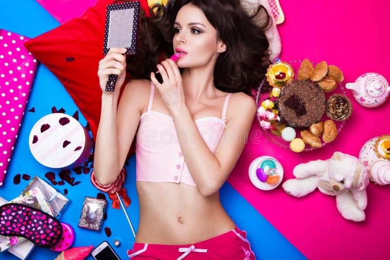 Mooie verse meisjespop die op heldere die achtergronden liggen door snoepjes, schoonheidsmiddelen en giften worden omringd De sti stock afbeeldingen