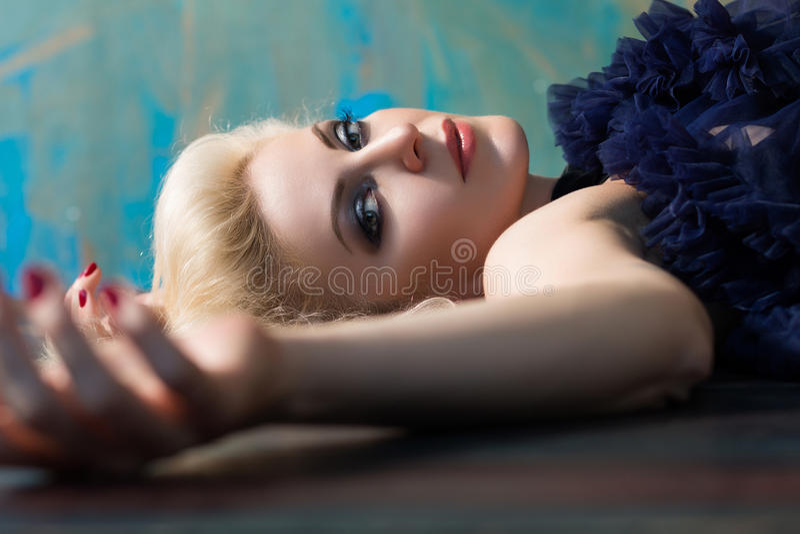 Mooie volwassen blondevrouw die op vloer leggen stock fotografie