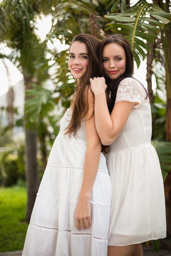 Mooie vrienden die in witte kleding glimlachen stock afbeeldingen