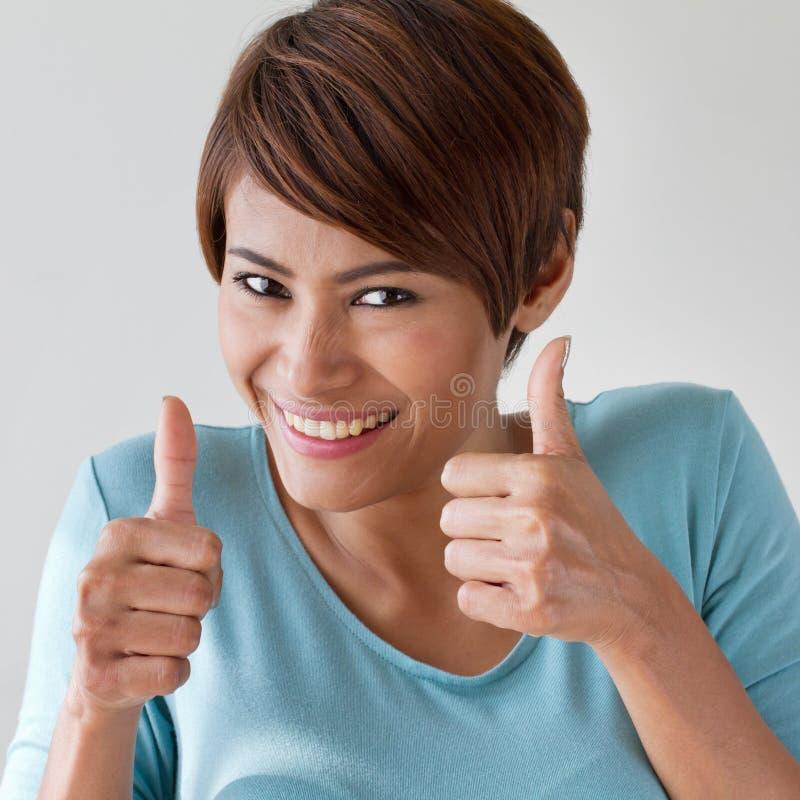 Mooie, vriendschappelijke, glimlachende vrouw die twee duimen opgeven stock afbeelding