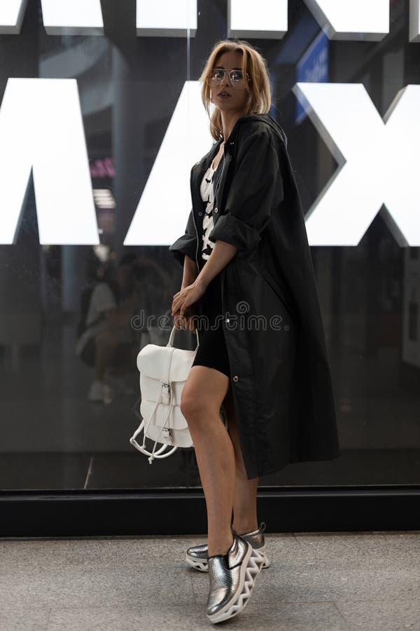 Mooie vrij jonge vrouw in modieuze kleren in glazen met een witte leerrugzak in zilveren schoenen die binnen stellen stock fotografie