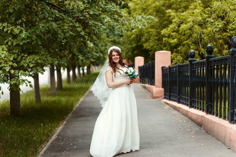Mooie vrolijke bruid in een witte kleding en sluier met een boeket in haar handen die de camera in het Park in de zomer bekijken royalty-vrije stock fotografie