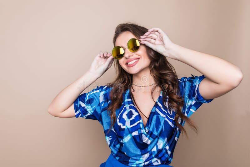 Mooie vrolijke de zomer jonge vrouw in zonnebril die zich over een kleurenachtergrond bevinden stock afbeelding