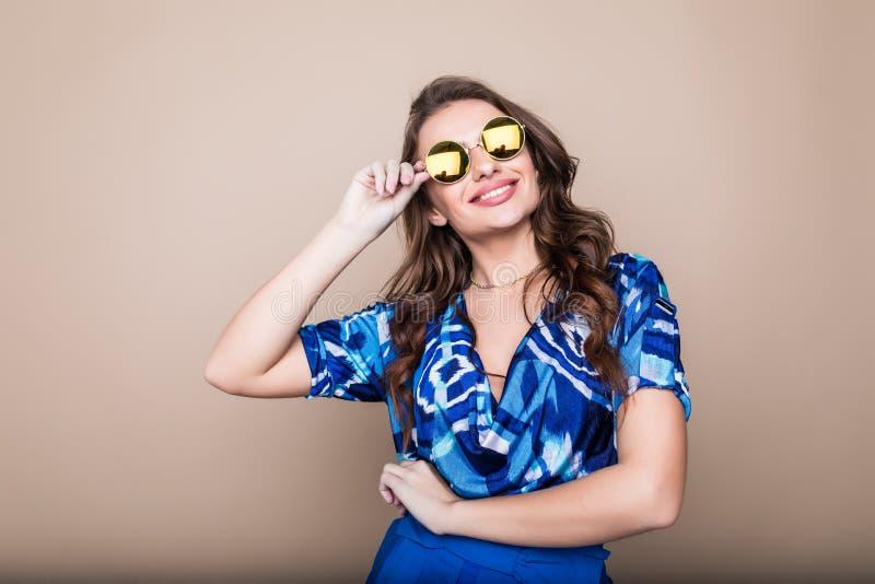 Mooie vrolijke de zomer jonge vrouw in zonnebril die zich over een kleurenachtergrond bevinden royalty-vrije stock foto