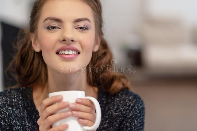 Mooie vrolijke jonge de koffiekop van de vrouwenholding royalty-vrije stock afbeeldingen