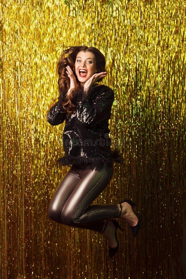 Mooie vrolijke vrouw die op fonkelende achtergrond springen Partij royalty-vrije stock foto's