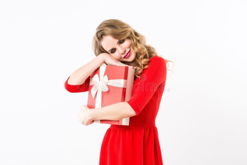 Mooie vrolijke vrouw in rode kleding met een gift over wit royalty-vrije stock fotografie