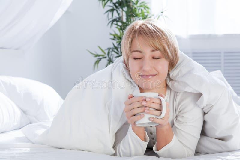 Mooie vrouw in bed in de ochtend, met een kop stock afbeeldingen
