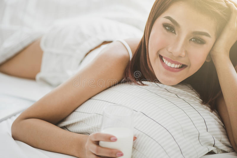 Mooie vrouw in bed met een kop van Melk stock fotografie