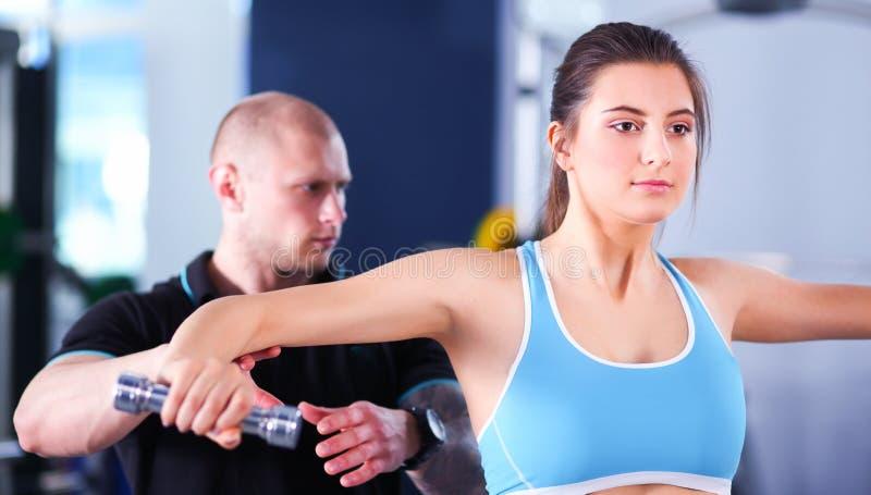 Download Mooie Vrouw Bij De Gymnastiek Die Met Haar Trainer Uitoefenen Stock Afbeelding - Afbeelding bestaande uit atletisch, oefening: 107705179