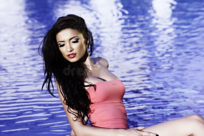 Mooie vrouw bij de pool stock afbeeldingen