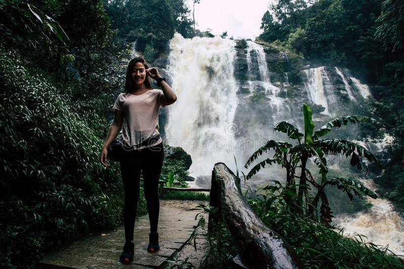 Mooie vrouw bij grote waterval na wandeling in Chiang Mai & x28; Thailand stock afbeelding