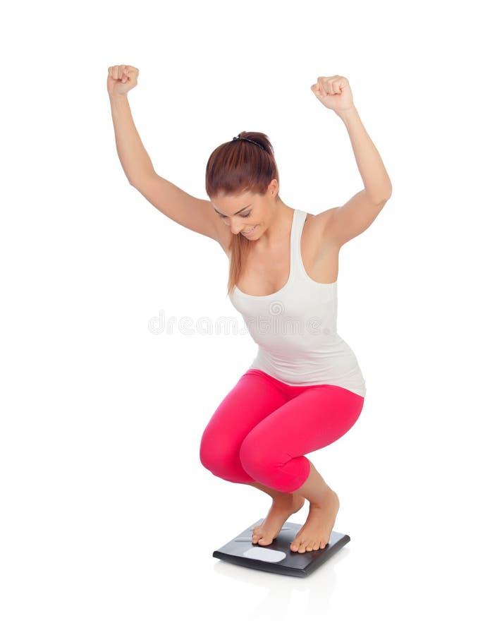 Mooie vrouw bij het zien van zijn nieuwe gewichtsschaal stock fotografie
