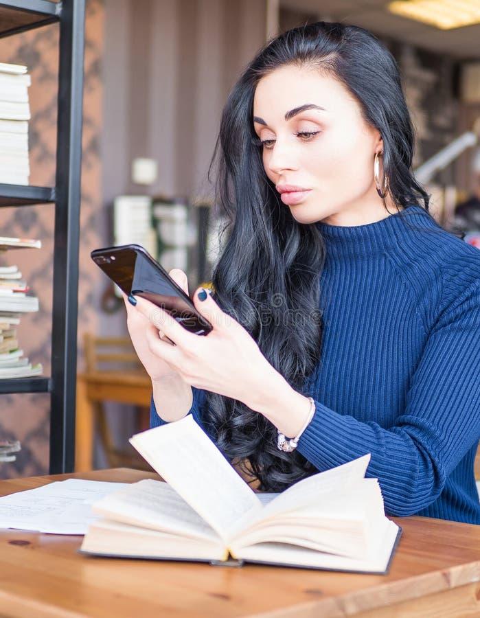 Mooie vrouw bij koffiewinkel Verzendt het persoons zijaanzicht, bericht door smartphone De boeken van de studentenlezing voor exa stock foto's