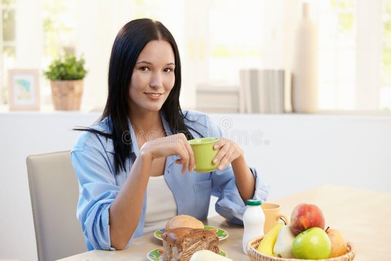 Mooie vrouw bij ontbijtlijst stock foto's